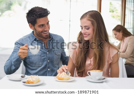 Smiling young couple having coffee at the coffee shop - stock photo