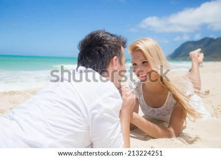 Smiling young couple holding hands and lying at beautiful summer sandy beach - stock photo