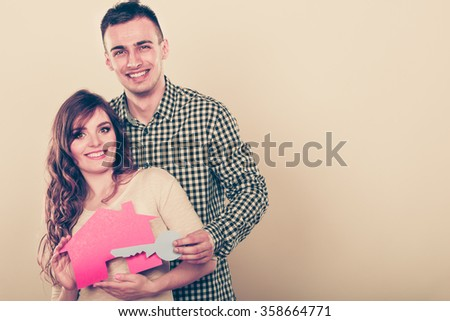 Smiling young couple holding paper house and key. Husband and wife dreaming about new home. Housing and real estate concept. Instagram filtered. - stock photo