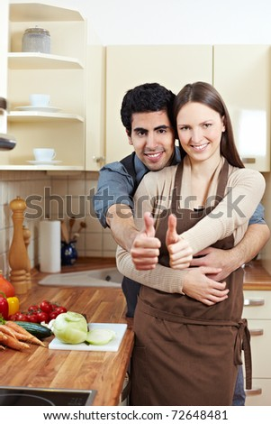 Smiling young couple holding their thumbs up in a kitchen - stock photo
