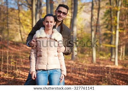 Smiling young couple in forest during autumn looking to camera - stock photo