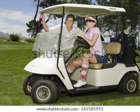 Smiling young couple in golf cart