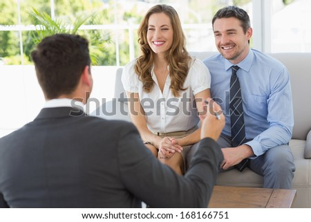 Smiling young couple in meeting with a financial adviser at home - stock photo