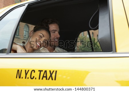 Smiling young couple in yellow taxi on urban street - stock photo