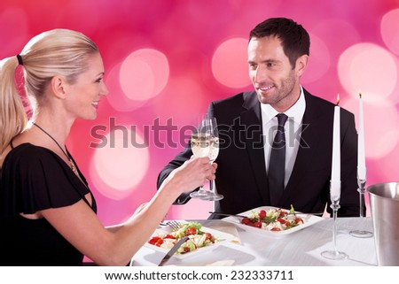 Smiling young couple looking at each other while toasting champagne flutes at restaurant table - stock photo