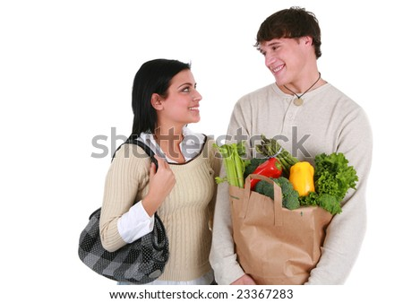 Smiling Young Couple Looking at Each Other with Groceries Shopping Items - stock photo