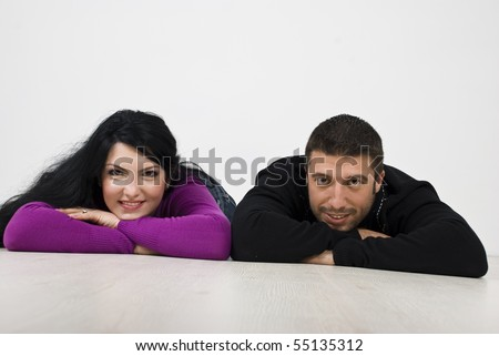 Smiling young couple lying down on floor and looking you - stock photo