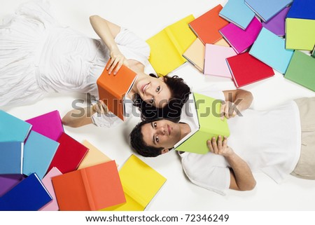 Smiling young couple lying on floor with colorful books and reading, looking up, isolated on white background. - stock photo