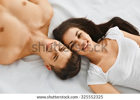 Smiling young couple lying together on the bed head to head.  Love and relationships lifestyle, interior bedroom.