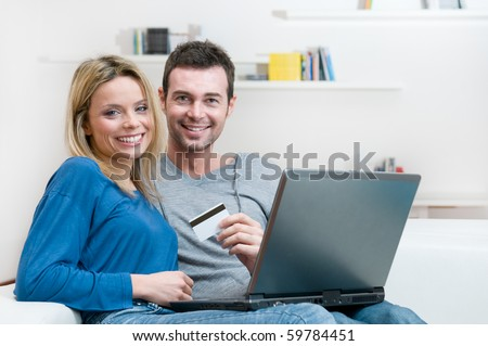 Smiling young couple making shopping online with credit card and laptop at home - stock photo