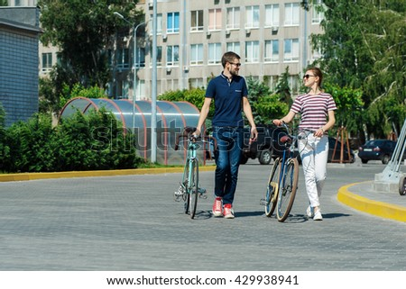 smiling young couple on the bicycle outdoors in city