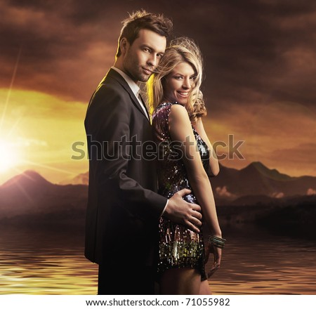 smiling young couple on the mountains background - stock photo