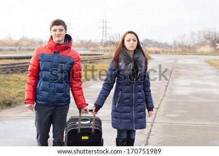 Smiling young couple pulling along a suitcase both holding onto the handle as they walk along a rural road alongside a railway line together - stock photo