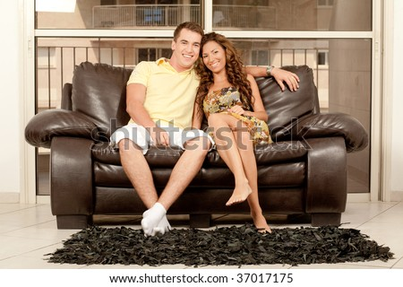 Smiling young couple seated on couch and looking at camera - stock photo