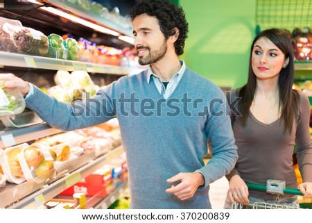 Smiling young couple shopping in a supermarket - stock photo