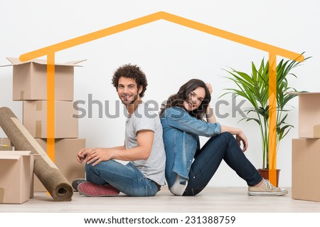 Smiling Young Couple Sitting Back To Back After Moving House - stock photo