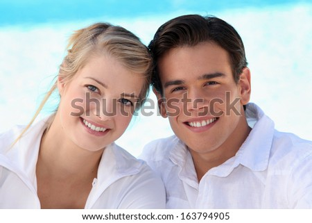 Smiling young couple sitting in the sunshine - stock photo