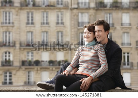 Smiling young couple sitting on bridge in front of town houses - stock photo
