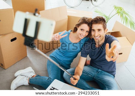 Smiling young couple sitting on their new house floor surrounded by cardboard boxes and taking selfies using a selfie stick - stock photo