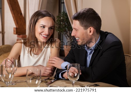 Smiling young couple waiting for dinner in restaurant - stock photo