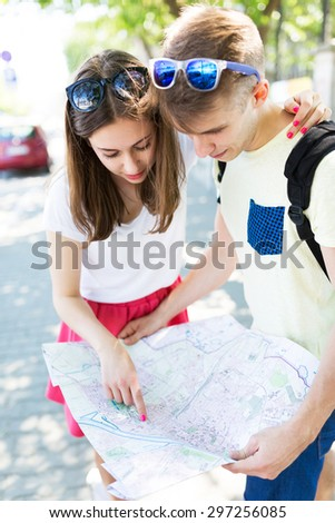 Smiling young couple with map  - stock photo