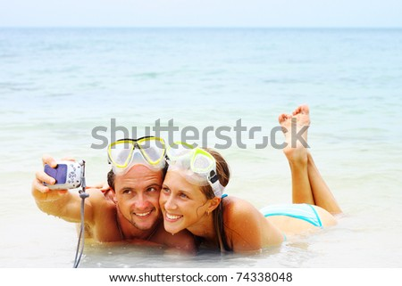 Smiling young couple with the masks making photo of themselves in the sea - stock photo