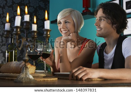 Smiling young couple with wineglasses enjoying dinner party - stock photo