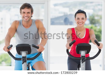 Smiling young couple working out at class in a gym - stock photo