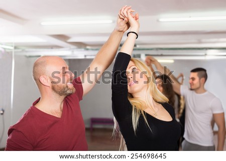 Smiling young couples enjoying of partner dance indoor - stock photo