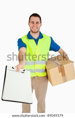 Smiling young delivery man handing over delivery note for signature against a white background - stock photo