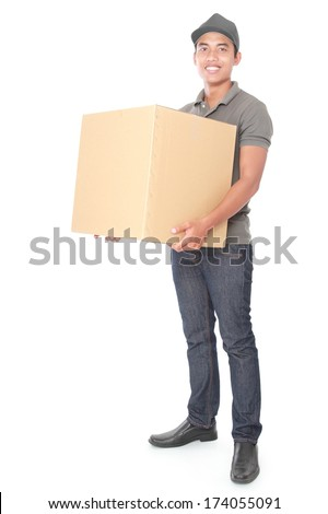 Smiling young delivery man holding and carrying a cardbox package isolated on white background - stock photo