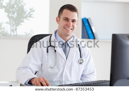 Smiling young doctor on his computer - stock photo