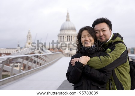 Smiling young East Asian couple at Millennium Bridge, St Paul's Cathedral in the distance. - stock photo