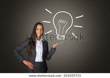 Smiling Young Executive Woman Showing Conceptual White Light Bulb Drawing on an Abstract Gray Gradient Background