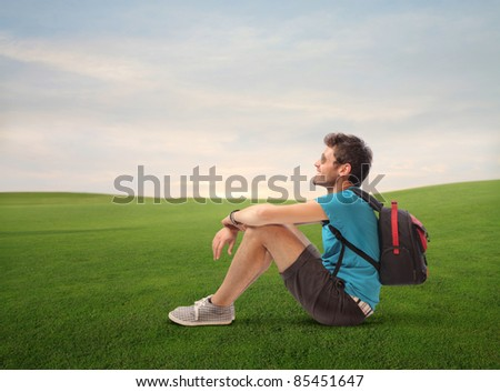 Smiling young explorer sitting on a green meadow - stock photo