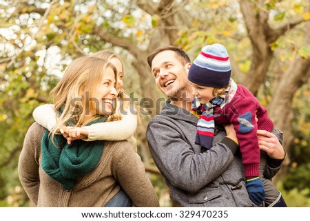 Smiling young family looking each other on an autumns day - stock photo