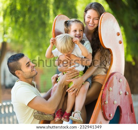 Smiling young family of four at children's playground in park. Focus on man - stock photo
