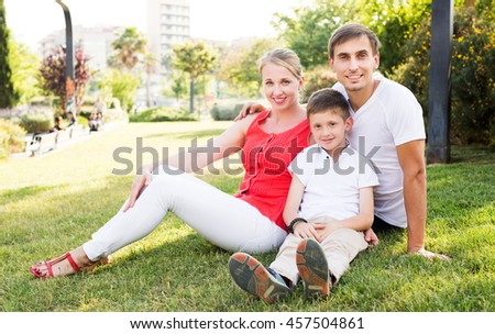 Smiling young family of three sitting together on green meadow in town on summer day - stock photo