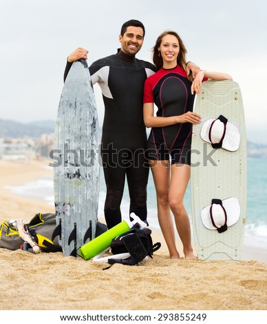 Smiling young family on the shore in wetsuits with surf boards - stock photo