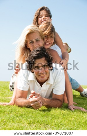 Smiling young family portrait looking at camera - stock photo