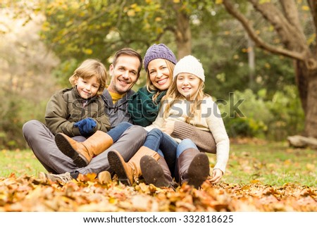 Smiling young family sitting in leaves on an autumns day - stock photo