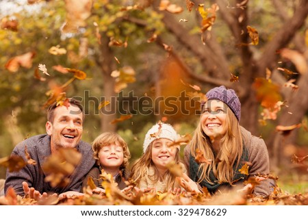 Smiling young family throwing leaves around on an autumns day - stock photo