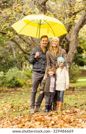 Smiling young family under umbrella on an autumns day - stock photo