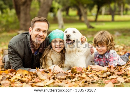 Smiling young family with dog on an autumns day - stock photo