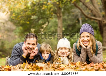 Smiling young family with hands on cheeks on an autumns day - stock photo