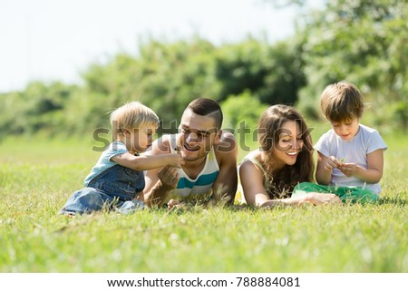 Smiling young family with little daughters laying in summer grass