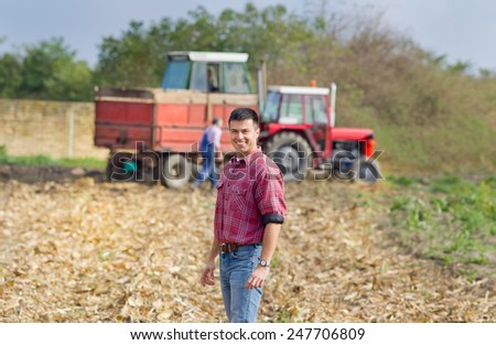 Smiling young farmer standing on field with tractor and trailer in background - stock photo
