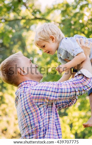Smiling, young father lifting his toddler son in the park.