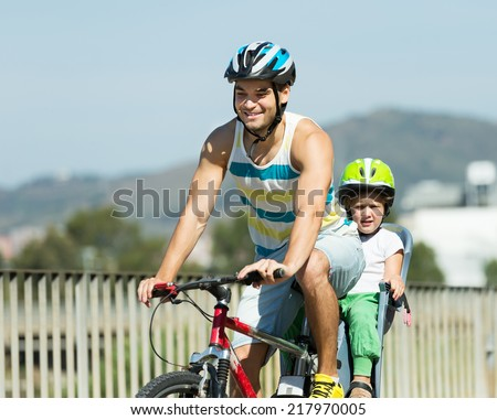 Smiling young father with daughter in helmets cycling though street