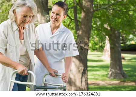 Smiling young female assisting mature woman with walker at the park - stock photo